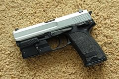 Handgun, semi-automatic. Semi-automatic handgun on carpet background, 9mm pistol Stock Photos