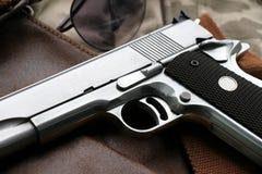 Handgun, semi-automatic. Semi-automatic handgun lying over a Leather handbag stock photography