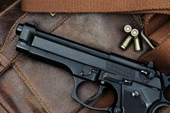 Handgun, semi-automatic. Semi-automatic handgun lying over a Leather handbag, 9mm pistol, Close-up royalty free stock photos