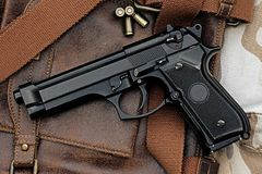 Handgun, semi-automatic. Semi-automatic handgun lying over a Leather handbag, 9mm pistol, Process HDR detail Stock Photos