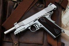 Handgun, semi-automatic. Semi-automatic handgun lying over a Leather handbag, .45 pistol royalty free stock photo