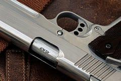 Handgun, semi-automatic. Semi-automatic handgun lying over a Leather handbag, .45 pistol, Close-up royalty free stock photos
