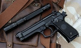 Handgun, semi-automatic. Semi-automatic handgun and tactical flashlight lying over a Leather handbag, 9mm pistol Royalty Free Stock Photo