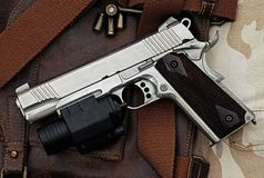 Handgun, semi-automatic. Semi-automatic handgun with tactical flashlight lying over a Leather handbag, 45 pistol, Process HDR detail stock photos