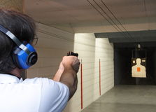 Handgun at shooting range. A Beretta 9mm handgun is being fired at an ondoor shooting range Stock Photos