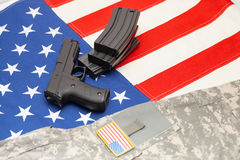 Handgun and US army uniform over USA flag Stock Photos
