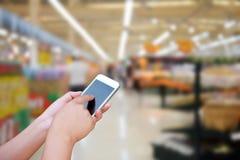 Handhåll för suddig bild och smart telefon för pekskärm på abstrakt begrepp Fotografering för Bildbyråer