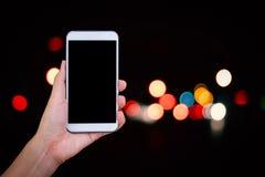 Handhåll och smart telefon för pekskärm på på abstrakt bokehbaksida Arkivbilder