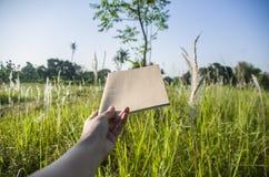 Handhåll på den bruna anteckningsboken med naturligt ljus i trädgården som är utomhus- på Chiang Ma, Thailand royaltyfria foton