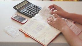 Handhaaf documentatie en de rekeningen, doen boekhouding met blkonot, de controles, de calculator en de telefoon 4K stock footage