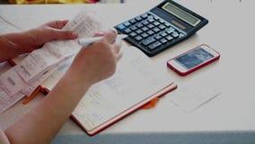 Handhaaf documentatie en de rekeningen, doen boekhouding met blkonote, de controles, de calculator en de telefoon, verslagaantall stock footage