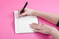 Handhandstil för ung kvinna genom att använda pennan i anteckningsboken som isoleras på rosa bakgrund Fotografering för Bildbyråer