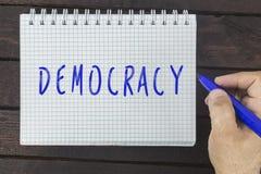 Handhandstil på notepaden: Demokrati royaltyfria bilder