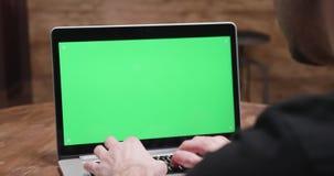Handheld съемка человека печатая на компьютере с зеленым экраном сток-видео