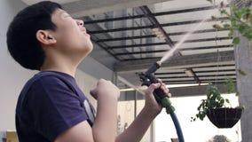 Handheld азиатского мальчика на солнечный горячий день, мальчик играет с водой и наслаждается им очень купая с водой видеоматериал