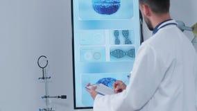 Handheld съемка доктора в его современном исследовательском центре принимая примечания на доске сзажимом для бумаги акции видеоматериалы