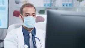 Handheld съемка доктора нося целебную маску работая на компьютере сток-видео