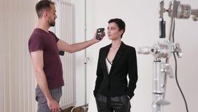 Handheld съемка фотографа используя светлый метр видеоматериал