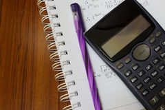 Handheld calculator on a sheet of paper. Maths concept - handheld calculator on a sheet of paper with maths-formulas Royalty Free Stock Photography