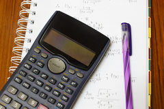 Handheld calculator on a sheet of paper. Maths concept - handheld calculator on a sheet of paper with maths-formulas Royalty Free Stock Photos