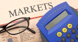 Handheld calculator and stock markets. With eyeglasses stock image