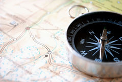 Handheld compass on a map. Handheld compass lying on a map showing the needle and cardinal points of north, south, east and west to aid in magnetic navigation to Stock Image
