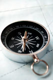 Handheld compass on a map Royalty Free Stock Image