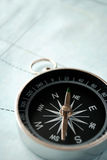 Handheld compass on a map Royalty Free Stock Photography