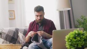 Handheld do homem novo que senta-se no sofá e no curso de confecção de malhas de observação no portátil
