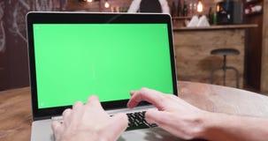 Handheld dynamiskt skott av snabbt skriva på en bärbar dator med den gröna skärmen stock video