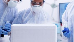 Handheld footage of amazed female scientist opening a chemical refrigerator box in modern laboratory. Scientist holding a smoking blue fluid in a tube stock footage