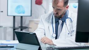 Handheld footage of doctor looking at tablet PC. In modern office or laboratory enviroment stock footage