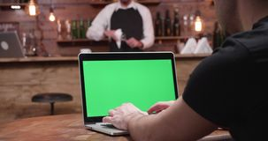 Handheld: Mantyper fastar på en modern bärbar dator med den gröna skärmen arkivfilmer