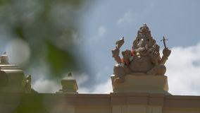 Ganesha Statue on Pillar. Handheld, medium close up shot of a Ganesha statue on an exterior pillar of a Hindu temple stock video