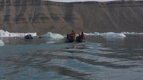 People In Raft On Icy Water Looking At Mountains