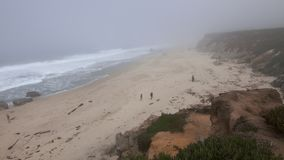 People on sandy cove during misty weather. Handheld, panning, aerial, medium wide shot of people on the beach of a cove during a misty, rainy day stock footage