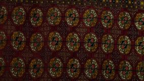 Fabric with Circular Emblems. Handheld, panning, close up shot of a piece of fabric containing circular patterns and symbols stock footage