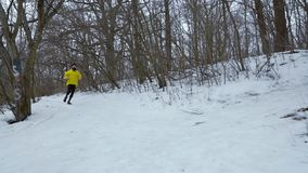 Handheld shot of bearded fit man running down the hill in winter forest. Male runner jogging on snow covered path among trees. sports, outdoors activities and stock video footage