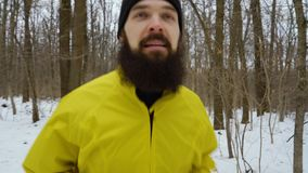 Handheld shot of bearded sportsman running towards camera in snowy winter forest. Runner athlete practicing on cold day. sports, outdoors activities and stock video footage