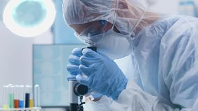 Handheld shot of chemist in high end laboratory. Looking at a microscope stock video
