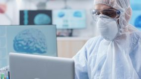 Handheld shot of chemist researcher working in modern laboratory. With 3D brain scans and DNA strings stock footage