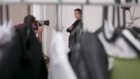 Handheld shot through clothes on the set of professional photoshoot. In the studio. Model and photographer are working together for the best image stock footage