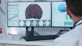 Handheld shot of doctor in front of 3D brain scan. Displayed on computer monitors in modern research facility stock video