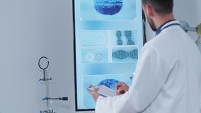 Handheld shot of doctor in his modern research center taking notes on a clipboard. While a 3D brain scan is displayed on the TV in the background stock video footage