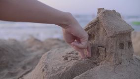 Sand House Model. Handheld shot of fingers walking home with sea waves in the backround. Real estate, house rental concept. Small building made of sand on the stock footage
