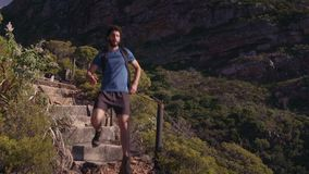 Male hiker moving down on cliff. Handheld shot of male hiker moving down on cliff steps during sunny day stock footage