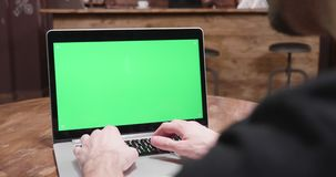 Handheld shot of man working on a computer with green screen. In a vintage interior stock footage