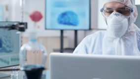 Handheld shot of professional chemist working in modern laboratory. Full of equipment and 3D brain scans stock footage