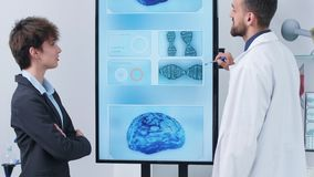 Handheld shot of researcher explaining something to a woman. In front of big screen with 3D brain simulation running on it stock footage