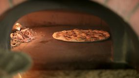 Handheld shot of vegetarian pizza cooking baking in the oven stock video footage